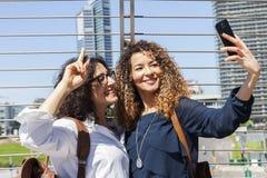2 усмехаясь симпатичных девушки принимают selfie Стоковые Изображения RF