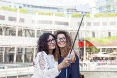 2 усмехаясь симпатичных девушки принимают selfie с smartphone Стоковое фото RF