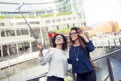 2 усмехаясь симпатичных девушки принимают selfie с smartphone Стоковая Фотография RF