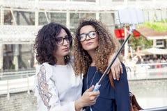 2 усмехаясь симпатичных девушки принимают selfie с smartphone Стоковое Фото