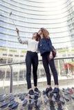 2 усмехаясь симпатичных девушки принимают selfie с smartphone Стоковые Изображения
