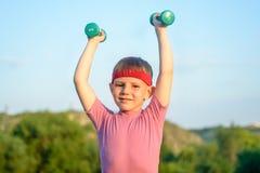 Усмехаясь сильный мальчик поднимая 2 гантели Стоковое Изображение