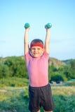Усмехаясь сильный мальчик поднимая 2 гантели Стоковые Фото