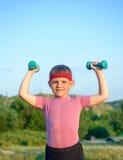 Усмехаясь сильный мальчик поднимая 2 гантели Стоковые Фотографии RF