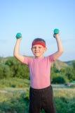 Усмехаясь сильный мальчик поднимая 2 гантели Стоковая Фотография