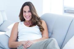 Усмехаясь склонность беременной женщины на софе Стоковое Фото