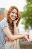Усмехаясь склонность женщины на мосте звоня телефонный звонок Стоковые Изображения RF