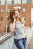Усмехаясь склонность женщины на мосте звоня телефонный звонок Стоковая Фотография RF