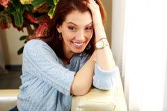 Усмехаясь склонность женщины на софе Стоковое Фото