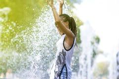 Усмехаясь смешная Афро-американская девушка подростка с Dreadlocks наслаждаясь в фонтане Стоковая Фотография
