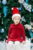 усмехаясь смешной кавказский малыш девушки ребенка с голубыми глазами в красном платье и шляпе Санта Клауса сидя на коробке сути  Стоковое Фото