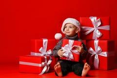 Усмехаясь смешной ребенок в шляпе Санты красной держа подарок рождества в руке Принципиальная схема рождества стоковая фотография rf