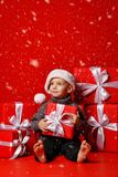 Усмехаясь смешной ребенок в шляпе Санты красной держа подарок рождества в руке Принципиальная схема рождества стоковое фото rf