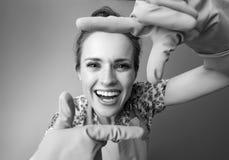 Усмехаясь современная домохозяйка обрамляя с руками дальше стоковое изображение