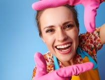 Усмехаясь современная домохозяйка обрамляя с руками на сини стоковая фотография rf