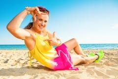 Усмехаясь современная женщина на береге моря обрамляя с руками стоковое фото