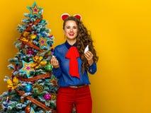 Усмехаясь современная женщина около рождественской елки держа носовой брызг Стоковые Изображения RF