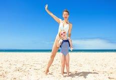 Усмехаясь современные мать и ребенок на seashore имея время потехи Стоковая Фотография RF