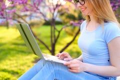 Усмехаясь сообщение девушки печатая компьтер-книжкой с предпосылкой цветения Стоковая Фотография RF