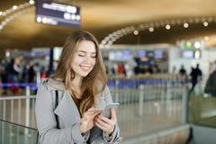 Усмехаясь сообщение женщины печатая smartphone на авиапорте, нося пальто Стоковое Фото