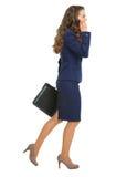 Усмехаясь сотовый телефон бизнес-леди идя косой говоря стоковые изображения rf