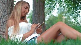 Усмехаясь сотовый телефон молодой женщины касающий и лежать на луге акции видеоматериалы