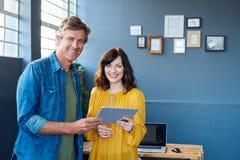 Усмехаясь сотрудники используя таблетку совместно в современном офисе Стоковые Изображения