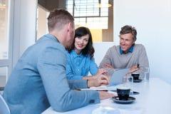 Усмехаясь сотрудники используя цифровую таблетку совместно в офисе Стоковые Фотографии RF