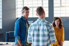 3 усмехаясь сотрудника говоря совместно в современном офисе Стоковые Изображения