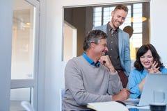 Усмехаясь сотрудники офиса говоря совместно пока использующ компьтер-книжку Стоковые Изображения RF