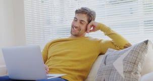 Усмехаясь софа молодого человека сидя используя его компьтер-книжку 4K 4k видеоматериал