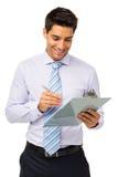 Усмехаясь сочинительство бизнесмена на доске сзажимом для бумаги стоковые фото