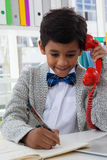 Усмехаясь сочинительство бизнесмена пока говорящ на телефоне наземной линии Стоковое Фото