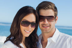 Усмехаясь солнечные очки и смотреть пар нося камеру Стоковая Фотография RF