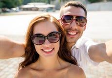 Усмехаясь солнечные очки пар нося делая selfie стоковые фото