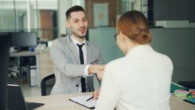 Усмехаясь специалист по набору персонала молодого человека говорит с успешным кандидатом молодой женщины после этого тряся ее рук сток-видео