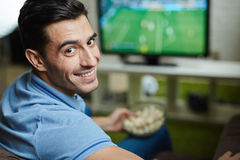 Усмехаясь спичка футбольного болельщика наблюдая Стоковые Изображения RF