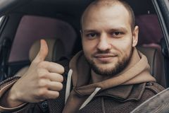 Усмехаясь спокойный человек сидя внутри автомобиля показывая большие пальцы руки вверх Положительная персона водителя Стоковая Фотография
