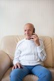Усмехаясь старик говорит на телефоне Стоковое фото RF
