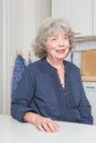 Усмехаясь старуха в кухне Стоковое фото RF