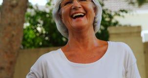 Усмехаясь старшая женщина держа циновку йоги в саде 4k видеоматериал