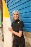 Усмехаясь старшая женщина держа surfboard пока готовящ голубую деревянную хату Стоковые Изображения