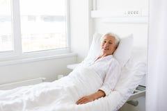 Усмехаясь старшая женщина лежа на кровати на больничной палате стоковые фото