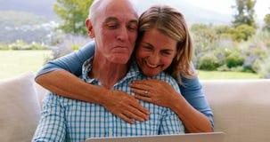 Усмехаясь старшая женщина обнимая человека в живущей комнате пока использующ компьтер-книжку видеоматериал