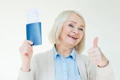 Усмехаясь старшая женщина показывая пасспорты с билетами и большим пальцем руки вверх, путешествующ концепция Стоковое Изображение RF