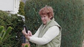 Усмехаясь старшая женщина принимая selfie мобильным телефоном в саде видеоматериал
