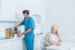 усмехаясь старшая женщина смотря социальный работника лить горячий напиток стоковые фотографии rf