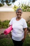 Усмехаясь старшая женщина стоя с циновкой тренировки на парке Стоковые Фото