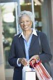 Усмехаясь старшая женщина с хозяйственными сумками Стоковое Изображение RF