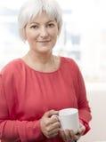 Усмехаясь старшая женщина с чаем Стоковые Фотографии RF